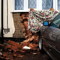 Van smashes car through house wall