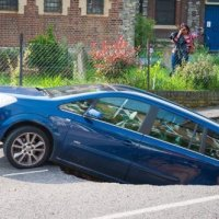 Sinkhole partly swallows family car